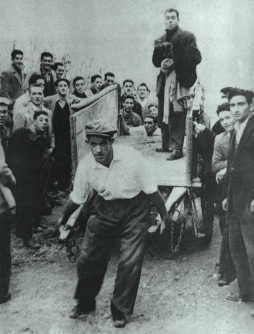 Hombre en el carro. Archivos del Ayuntamiento. Foto de 1950. Aparecen Nicolás Eguiluz, Julio Pérez, Pedro Arinas, Adolfo Saiz, Jesús Quintana, Serapio Martínez, José Luis López, Eloy Lanzo